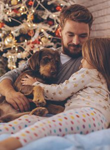 Dad and daughter cuddle dog with Christmas Tree in background
